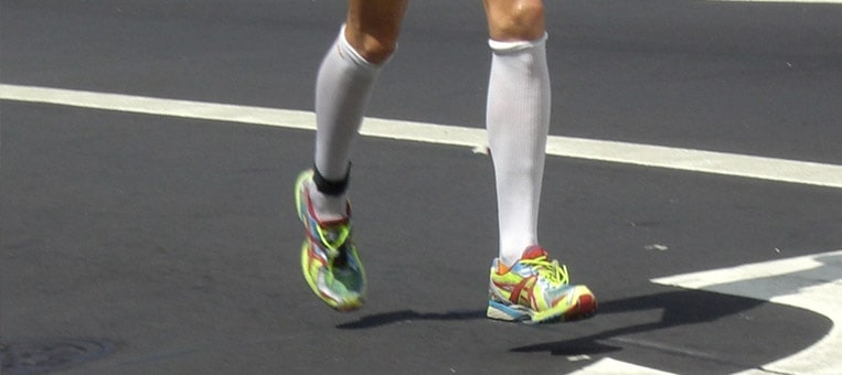 close nas pernas de um corredor utilizando meias de compressão na cor branca